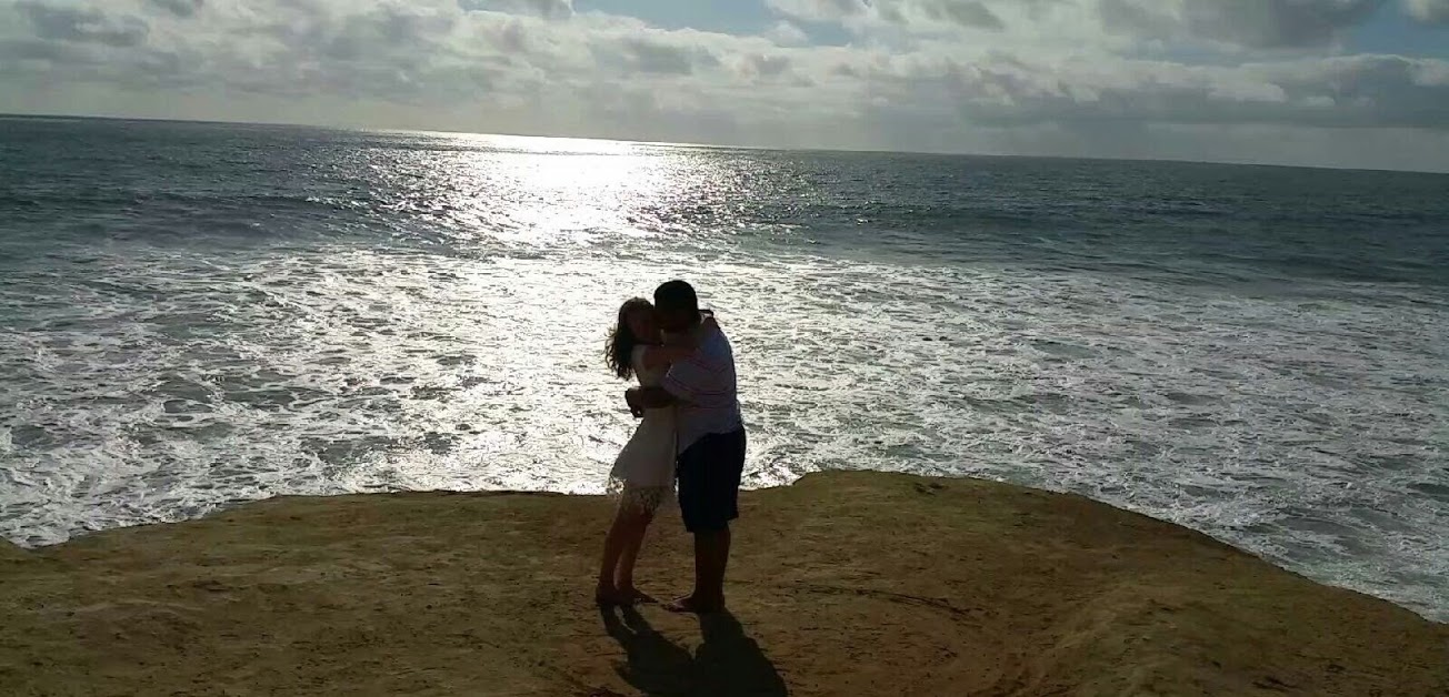 Newly engaged fiances embracing by the Pacific Ocean