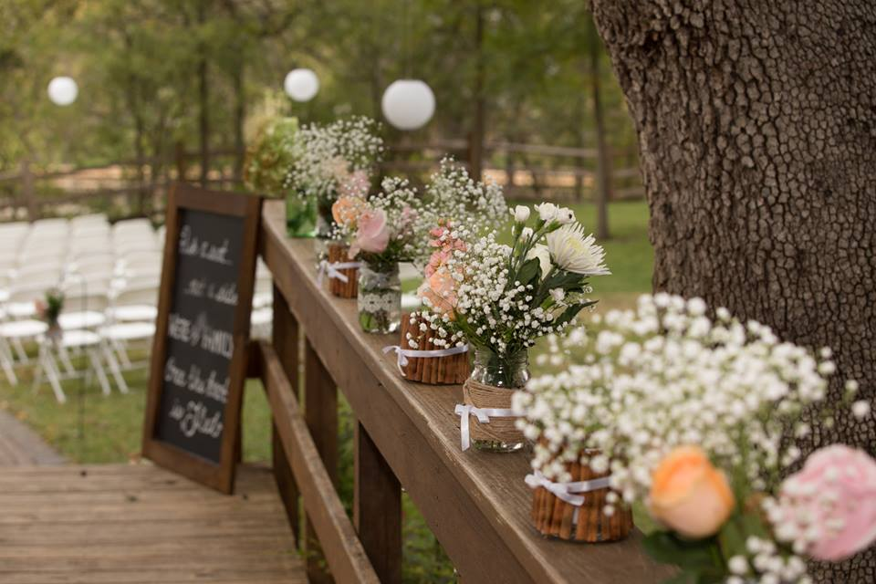 Row of mason jar floral decor at wedding venue, with lanterns and chalkboard welcome sign in the background