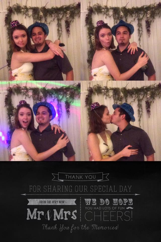 Man and woman posing in front of DIY wedding photo booth with props