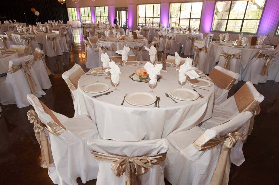 Wedding reception area set up with round tables draped with white cloths and chairs wrapped with gold bows.