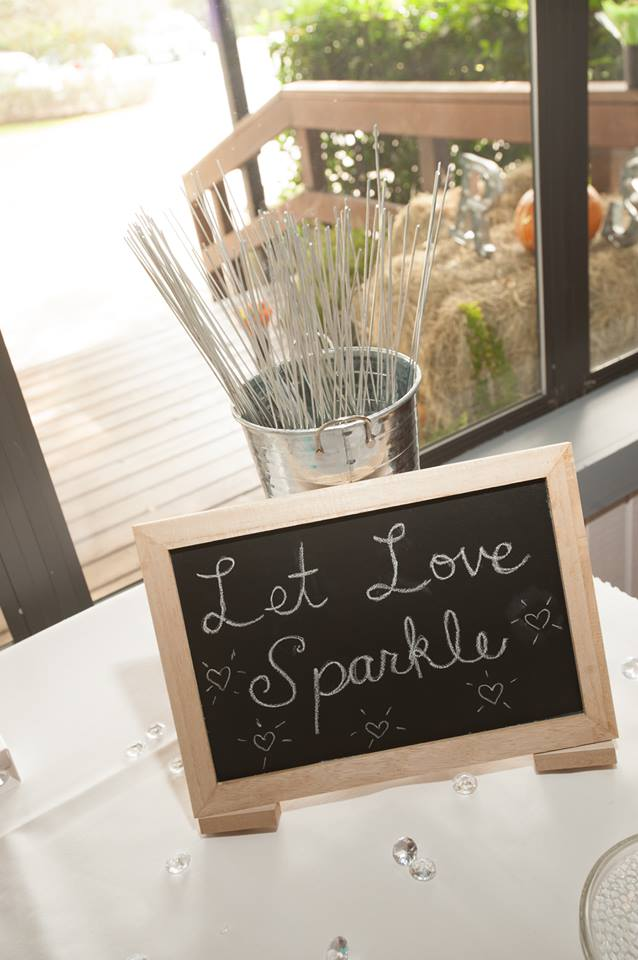 Sparklers for wedding send off next to chalkboard sign stating let love sparkle