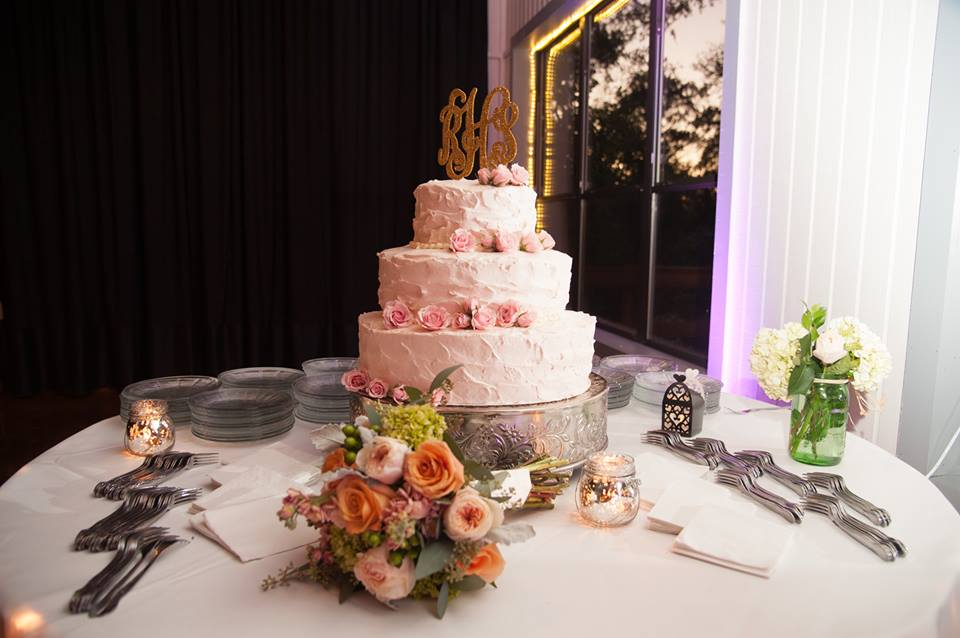 White wedding cake with pink roses, and gold glitter monogram cake topper on silver cake stand surrounded by mason jar bouquet, candles, silverware, and bridal bouquet of flowers