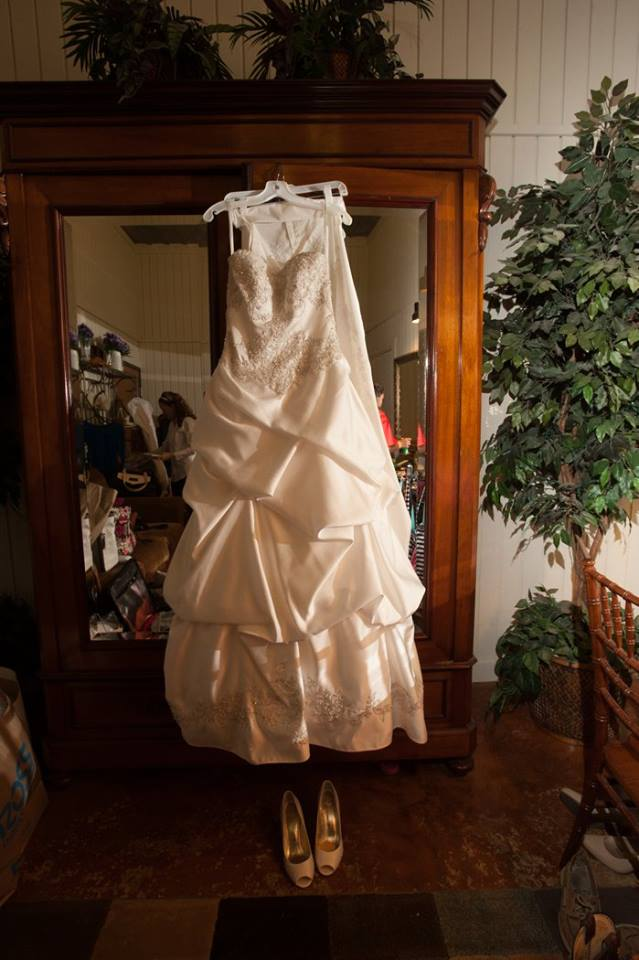 White wedding dress hanging on armor above white satin heels