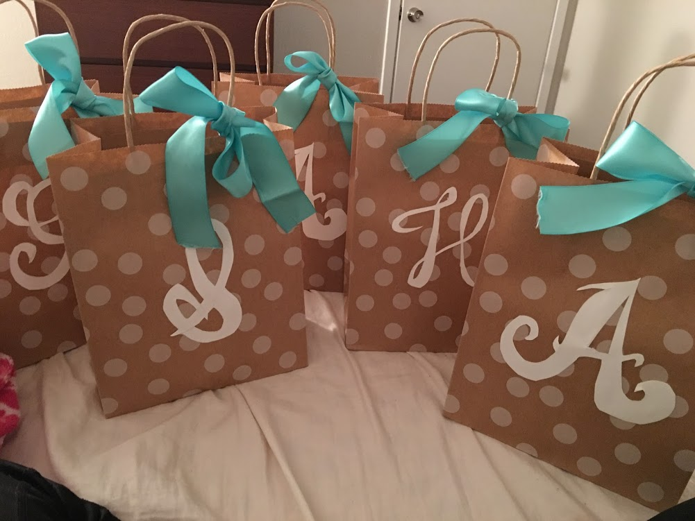 Brown paper bags with polka dots and hand cut white lettering with blue bows tied around the handles for bridal party
