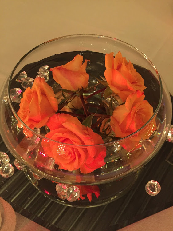 Wedding centerpiece with coral roses floating in water in round bowl over a mirror with tea light candles and jewels