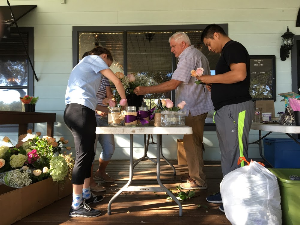 Wedding party showing how to do wedding flowers standing at a table creating floral arrangements DIY