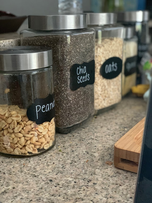 Glass jars with chalkboard labels for bulk peanuts, chia seeds, oats, and quinoa on granite countertop