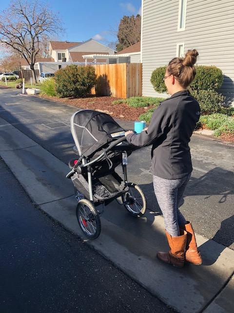 natural postpartum mom pushing stroller