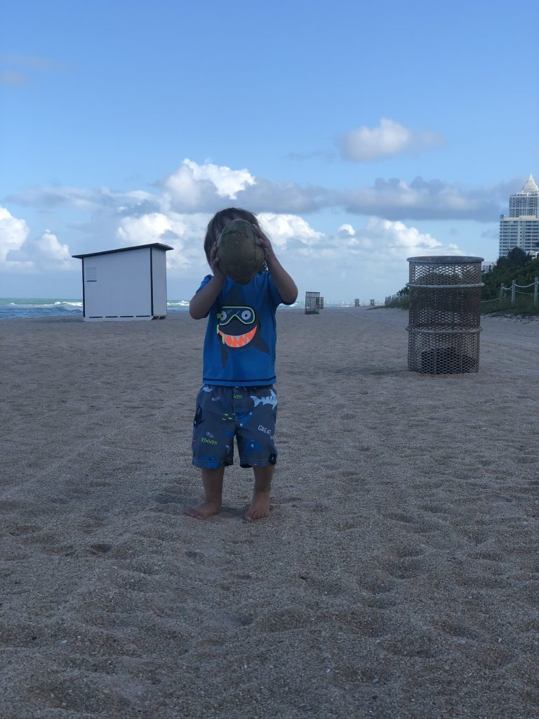 toddler holding coconut on Miami Beach